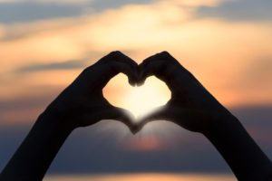 A brief Valentine's Day History - two hands making a heart shape with sunset inside them.